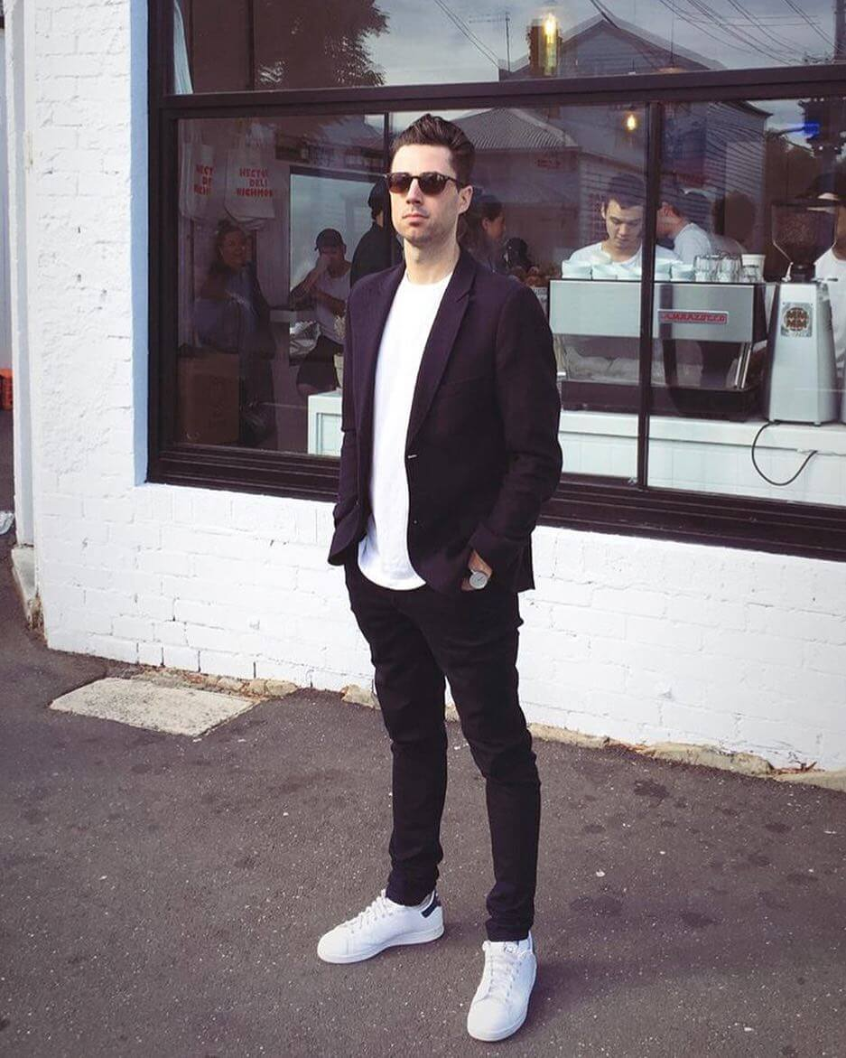 Ch'an standing outside of a coffee shop dress in white sneakers and sunglasses