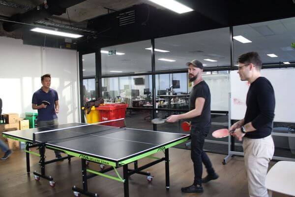 Members of the DesignOps meetup playing table tennis