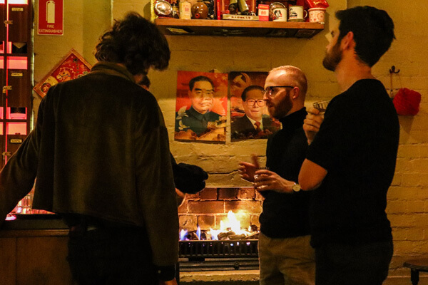 Adam and some members standing around an open fireplace, talking and drinking