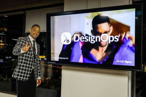 Cardboard cutout of Will Smith standing next to a TV with an image of Will Smith